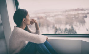 a person looking out the window. This photo could represent a person seeking treatment for depression. Depression treatment can be sought through online therapy in North Carolina and Florida. Learn more today! 27260